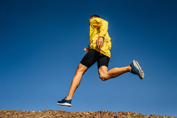 man runner in yellow sports jacket run on blue sky background