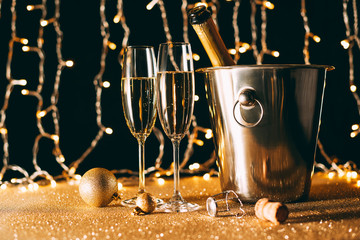 two glasses and champagne bottle in bucket on garland light background, christmas concept