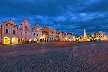 Classic wide-angle view of main square of Telc with renaissance and baroque colorful houses. Public fountain with statue of st. Margaret and Plague Column. Summer evening with dramatic sky