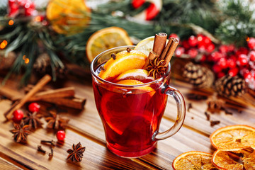 Christmas mulled red wine with spices and fruits on a wooden rustic table. Traditional hot drink at winter time