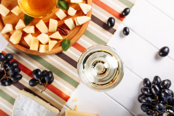 Glass of white wine, Cheese plate with mozarella, parmesan, honey and grapes on table. Top view selective focus