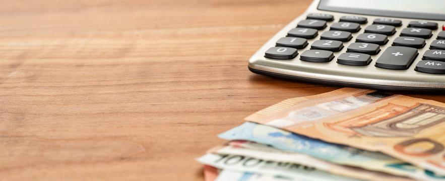 Taschenrechner und Geldscheine mit Textfreiraum
