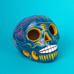 Creative and minimal Day of the Dead or Halloween layout. Skull on blue paper background. Flat lay front view. Square format.