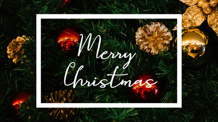 Merry Christmas word written inside white graphic frame with Christmas tree decorated with ornaments in background.