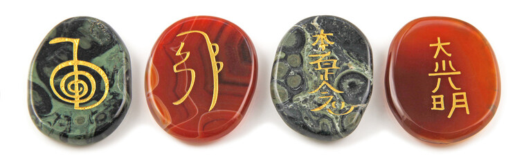 The four major Reiki Healing Symbols - etched into palm stones made of Carnelian and Kambaba Jasper placed in a neat row against a white background