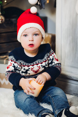 Portrait of little blonde boy sitting on roof in decorated studio and playing with Christmas presents and boxes. Decoration of winter forest, trees and snow effect on background. Concept of Christmas