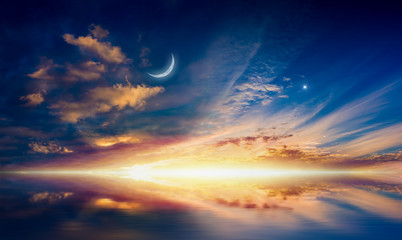 Crescent moon, glowing clouds and bright star are reflected in serene sea