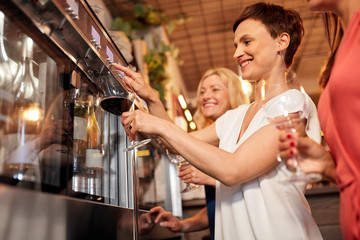 people, alcohol and lifestyle concept - happy women with glass pouring red wine from dispenser at bar or restaurant