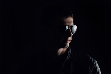 Young man's portrait. Close-up of serious young man in a black leather jacket and sunglasses on black background