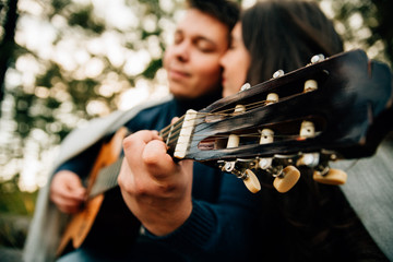 young man playing guitar while woman smiling on meadow