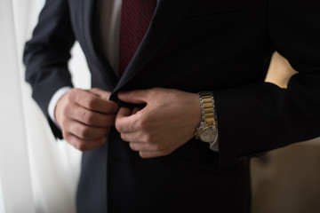groom in a jacket, the groom fastens his jacket, business style, man fastens his jacket