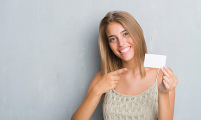 Beautiful young woman over grunge grey wall holding blank visit card very happy pointing with hand and finger
