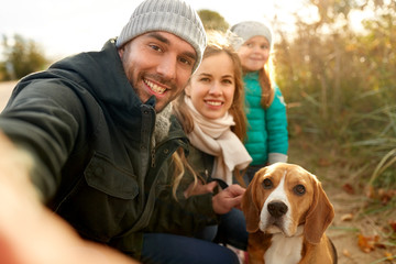 family, pets and people concept - happy mother, father and little daughter with beagle dog taking selfie outdoors in autumn