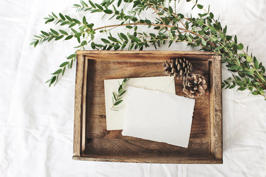 Christmas or winter wedding mock-up scene. Blank cotton paper greeting cards, old wooden tray, pine cones and green Eucalyptus parvifolia branch.White bed linen background. Flat lay, top view.