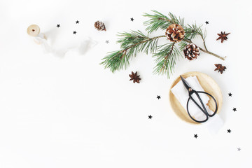 Christmas craft composition. Decorative corner made. Pine branch with cones, silk ribbons, vintage scissors on wooden plate, black confetti and anise stars. White table background. Flat lay, top view