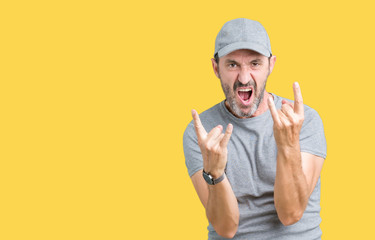 Handsome middle age hoary senior man wearing sport cap over isolated background shouting with crazy expression doing rock symbol with hands up. Music star. Heavy concept.