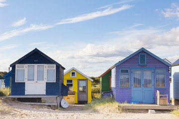 Colourful beach huts under a blue sky.