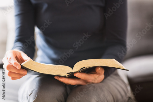 Woman Reading from an Open Bible at Home  Bible Study Concept