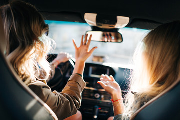 Image of back of two talking women with long hair sitting in car