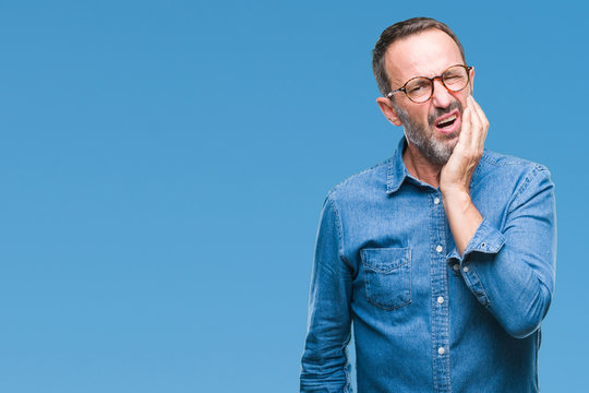 Middle age hoary senior man wearing glasses over isolated background touching mouth with hand with painful expression because of toothache or dental illness on teeth. Dentist concept.