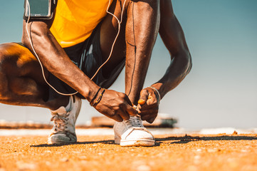 Close up of a black man hands tying shoelaces before training starts