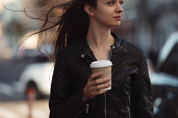 Woman enjoying to walking with coffee cup in city street
