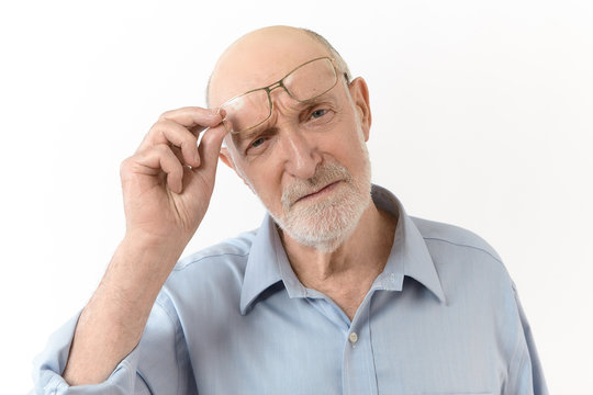 People, aging, eyewear, vision and optics concept. Horizontal image of long sighted elderly man with white beard taking off his spectacles and frowning to see clearly what is in front of him