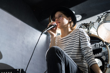 Low angle portrait of beautiful young woman singing to microphone during band rehearsal in studio, copy space