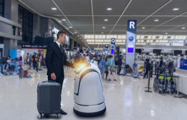 Smart robotic technology concept, The passenger follow a service robot to a counter check in in airport, the robot can help and give some information to passenger quickly