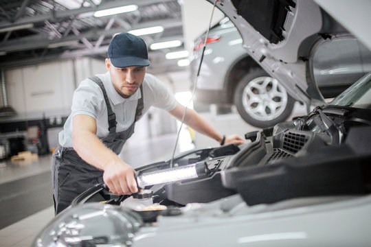 Serious and concentrated man stands at opened body of car and repair details in it. He is calm and concentrated. Guy holds wrench in hand. He uses it.