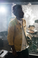 Waist up portrait of contemporary African-American man smoking during band rehearsal in recording studio