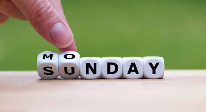 Hand is turning dice and changes the word Sunday to Monday