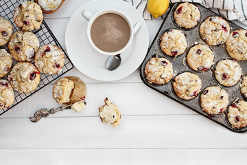 Hot steaming coffee and cranberry muffins with butter over a rustic white table background. Image shot from above with free space for text.