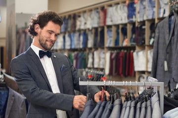 Man in store searching for perfect upper part of costume.