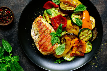 Grilled chiken fillet with vegetables.Top view.