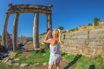 Travel woman photographer takes shot of Doric Propylon in Ancient Messene, Historical Site, Peloponnese, Greece. Seductive caucasian model photographing a Greek Temple. Europe summer travel concept.