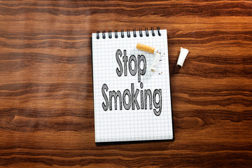 stop smoking text in notebook and  cut, broken cigarette on wood table