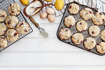 Cranberry Muffins in a muffin tin with fresh eggs, sugar, lemons and lemon zest over a rustic white table background. Image shot from above with free space for text.