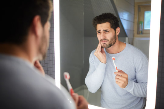 Sad frowning handsome brunette young man with beard touching cheek and looking into mirror in bathroom while getting bad tooth during cleaning teeth