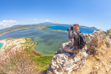Travel female takes shots of scenic Voidokilia Beach from Navarino Castle ruin in Pylos, Peloponnese, Greece after hiking.Hiker woman photographing a popular greek landmarks. Fish eye view