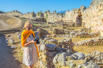 Traveler woman photographer at of Archaeological Site of Ancient Mycenae, Peloponnese, Greece. Caucasian beauty blonde female photographing a ruins of defence stone walls. Europe Heritage Site