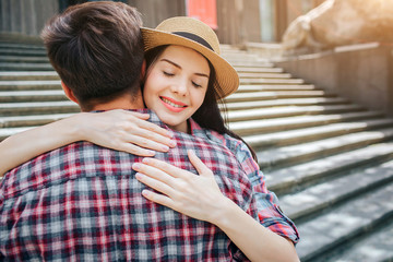 Positive picture of young woman embracing her man. She smiles and keeps eyes closed. She wears hat. They stand on stairs.