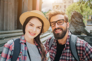 Nice picture of two young tourists looking on camera and smiling. Man and woman stand outside close to stairs. They have rocksacks on back. People are positive and beautiful.
