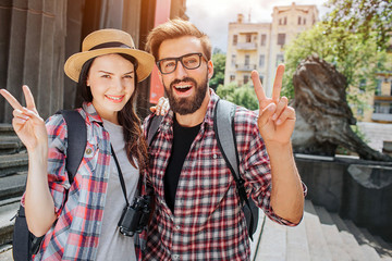Happy and positive travellers stand outside close to steps and pose on camera. They show piece symbol. Woman has binoculars. They look nice and lovely.