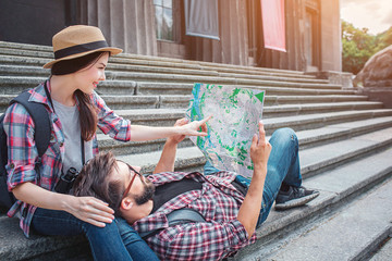 Nice picture of young tourists on stairs. She sits there and points on map. He holds map and lies on woman's knees.