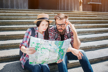 Two tourists sitting on steps and hold map together. They look at it. People are concentrated and serious.