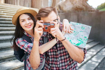 Happy tourists stand outside and pose. She smiles and embrace her boyfriend. He takes pictures by holding camera in hands. Female tourist has map in hands.