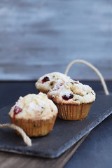Cranberry Muffins with lemon sugar topping on a rustic slate serving tray. Extreme shallow depth of field with selective focus on muffin in center.