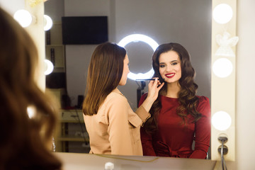 Make up artist doing professional make up of young woman. School of make-up artists.