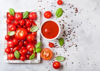 Glass of fresh organic tomato paste with fresh raw tomatoes basil and pepper in box on stone kitchen background